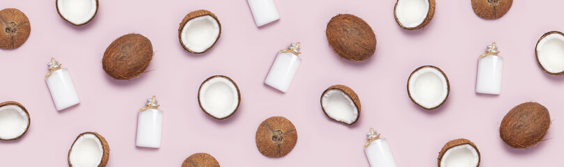 Pattern with ripe coconuts and coconut oil in a glass bottle on pink background minimal flat lay style. Tropical abstract background Top View Copy Space. Pop art design, Natural cosmetic concept.