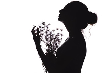 silhouette of a beautiful girl with a bouquet of dried flowers, face profile of a young woman looking upwards on a white isolated background