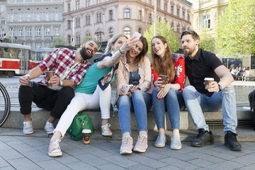 best friends take a group selfie downtown and enjoy carefree lifestyle with coffee to go