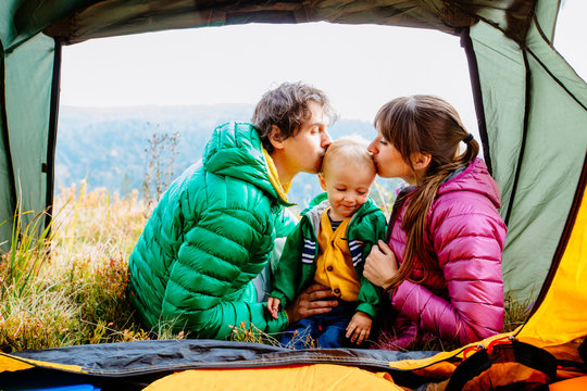 Happy family of three in camping trip - father, mother kiss toddler child son sitting entrance of tent, relaxing, enjoying view at Carpathian mountain. Travel with children, health relations concept.