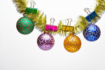 Christmas ornaments concept. Tinsel with pinned christmas balls or ornaments, white background, copy space. Balls with glitter ornaments hang on shimmering golden tinsel