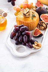 Cheese plate served with grapes, jam, figs, crackers and nuts on a white background. Copy space.