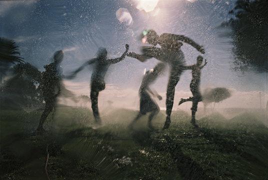 Friends playing in water sprinkler