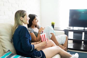 Women Enjoying TV Show While Sitting On Sofa