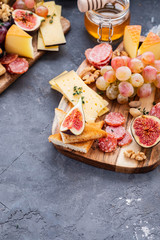 Cheese plate served with grapes, jam, figs, honey, crackers and nuts on a grey background. Copy space.