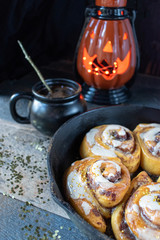 magical Halloween cinnamon rolls with white icing and gold stars in cast iron pan