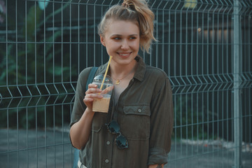 Carefree girl holding a big glass with a cold drink