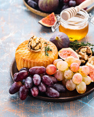Cheese plate served with grapes, jam, figs, honey and nuts on a rustic background. Copy space.