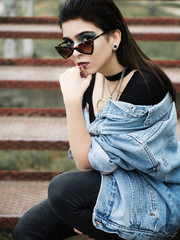 Young woman with sunglasses sitting outdoors