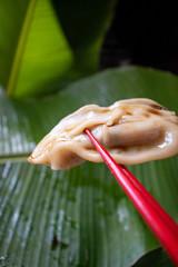 steamed steamed pot sticker dumpling in red chop sticks over green banana leaves