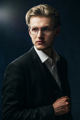 Waist up studio portrait of young confident handsome man, businessman wearing round glasses, classic white shirt, black jacket, posing on dark background