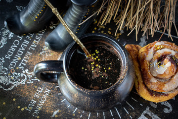 Magical Halloween coffee with gold stars and pumpkin cinnamon roll with witch shoes and broom