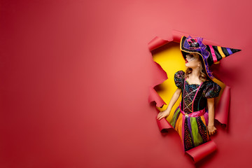 Happy Halloween. Laughing funny child girl in a witch costume of halloween looking to the side through a hole of red and yellow paper background. Copyspace