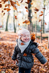 child is playing with leaves that have fallen from the tree