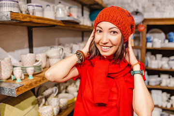 young woman trying and choosing warm hat in fashion store
