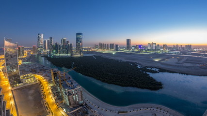 Buildings on Al Reem island in Abu Dhabi day to night timelapse from above.