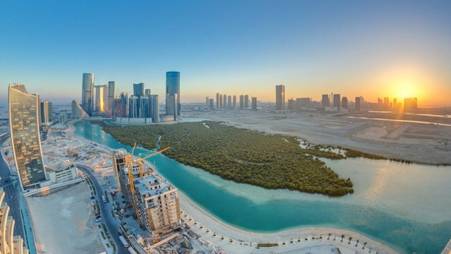 Buildings on Al Reem island in Abu Dhabi at sunset timelapse from above.