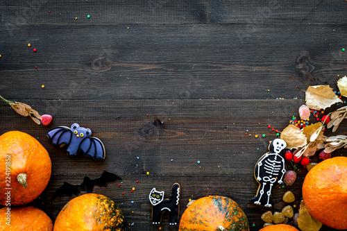 Halloween concept, halloween mood. Pumpkins and cute figures of halloween evils. Skeleton, bats. dark wooden background top view copy space
