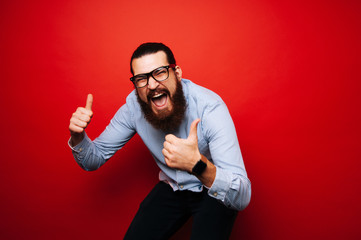 Cheerful bearded hipster man in casual with eyeglasses jump over red background and showing thumbs up and wearing smartwatch