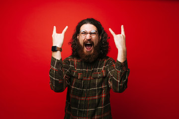 Portrait of bearded man with long curly hair showing rock sign and screaming