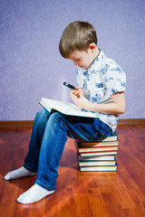 Little boy in a light shirt sits on a pile of books with a green book in his hands and looks through a magnifying glass