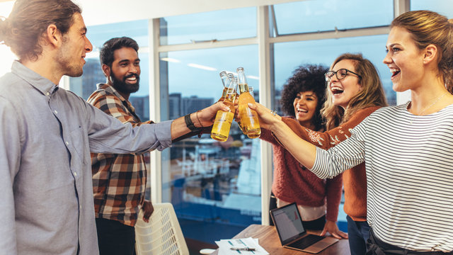 Coworkers celebrating success in office with drinks