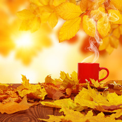 Autumn leaves and red cup of coffee .
