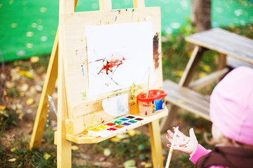 little girl draws  on the easel. the child paints