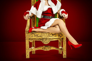 Christmas time and slim woman legs in red heels. Free space for your decoration.