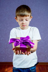 A little boy in a white T-shirt on a purple background holds a gift with a big bow and is sad