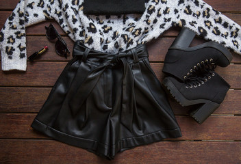 Fashionable women street style clothes: leopard sweater, boots, leather shorts.