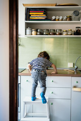 Little boy climbing on a countertop in his kitchen