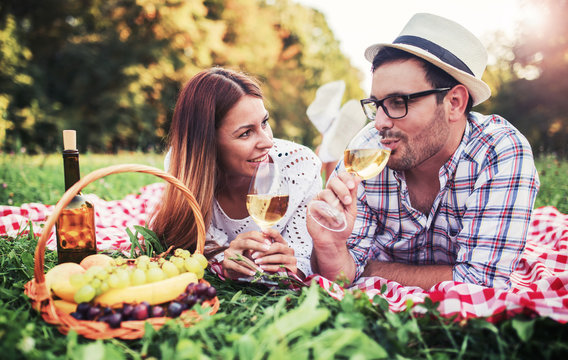 Loving couple enjoying picnic in the park. Love and tenderness, dating, romance, lifestyle concept