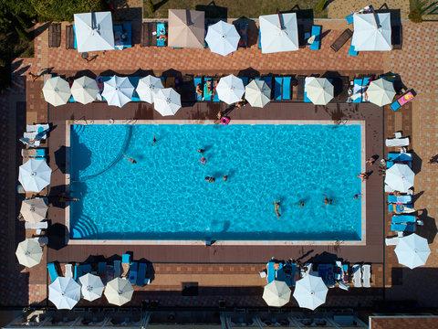 Aerial view on people in swimming pool. Top view of people sunbathing pool.