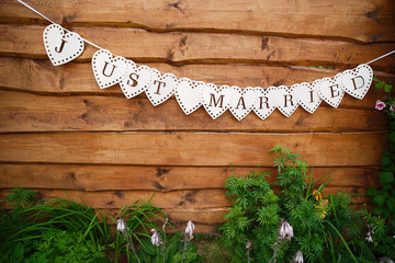 Hanging decorative flags with inscription Just Married. Lettering decoration, wooden wall as background. Text garland on the wall, Wedding invitation card. Vintage wooden background.