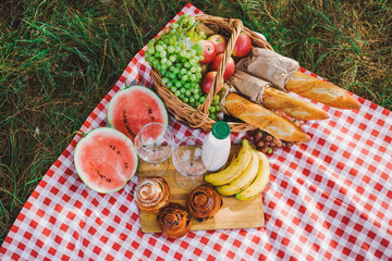 Healthy food for picnic outside. View from above of fresh buns, bread, yogurt, bananas, watermelon, green grape and red apples. Horizontal color image.