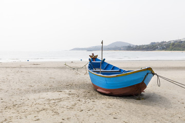 Blue fishing boat on sandy beach in Vietnam