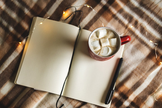 Autumn and winter background with notebook, pen, garland, mug of cocoa, coffee or hot chocolate with marshmallow on plaid. Concept of work, drawing up plans in warm cozy home environment.