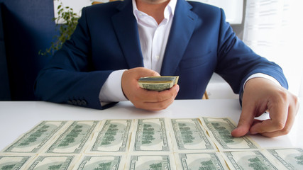 Closeup photo of successful businessman laying money in front of him on office desk