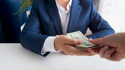 Closeup photo of businessman taking stack of money as bribe