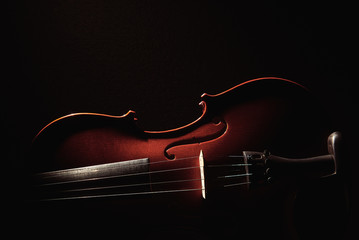 part of a violin on a black background with hard light