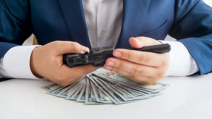 Closeup photo of businessman in suit with lots of money holding revolver in hands