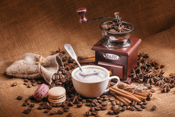 Coffee still life with wooden vintage grinder, Cezve, cup, coffee beans and cookies macarons.