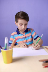 European boy spending time drawing with colorful pencils at home.