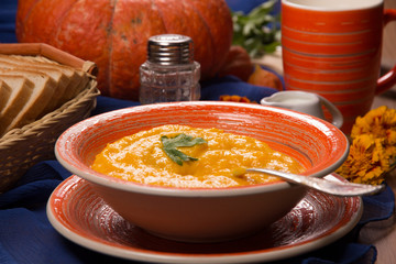 Pumpkin cream soup in a plate on the kitchen table