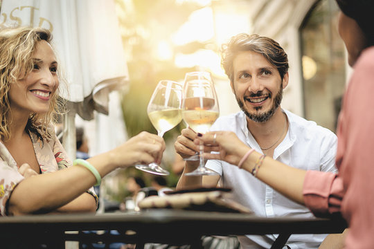 happy friends having fun outdoors - Mid age people enjoying time together at bar - 40s and friendship concept - Hands toasting red and white wine glass at city bar outdoor during sunset