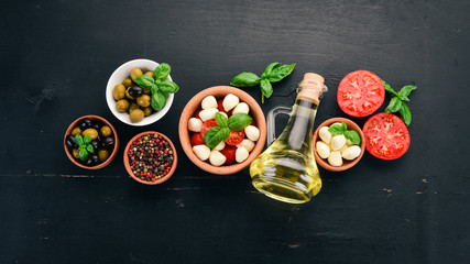 Ingredients for Italian caprese salad. Mozzarella cheese, cherry tomatoes, basil leaves, olives, oil, pepper. On a black wooden background. Free space for text.