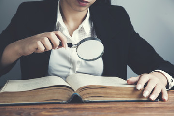 woman reading books hand magnifier