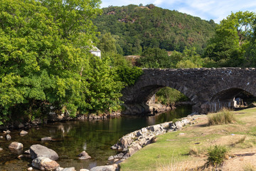 Old stone bridge over River Duddon in Ulpha in the Lake District National Park, UK. Scenic view of English countryside on a sunny day