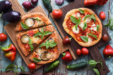 Healthy vegetarian food. Pizzas with eggplants, tomatoes and bell peppers on oak boards served with raw vegetables on shabby blue background